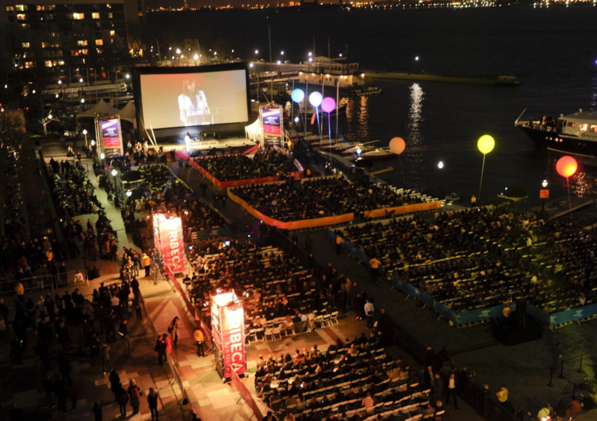 """FILE - People attend an outdoor screening  for """"The Union"""" at the opening night gala of the Tribeca Film Festival in New York on April 20, 2011. The Tribeca Film Festival said Monday, March 29, 2021, it plans to hold its 20th edition in-person and with outdoor screenings in June."""