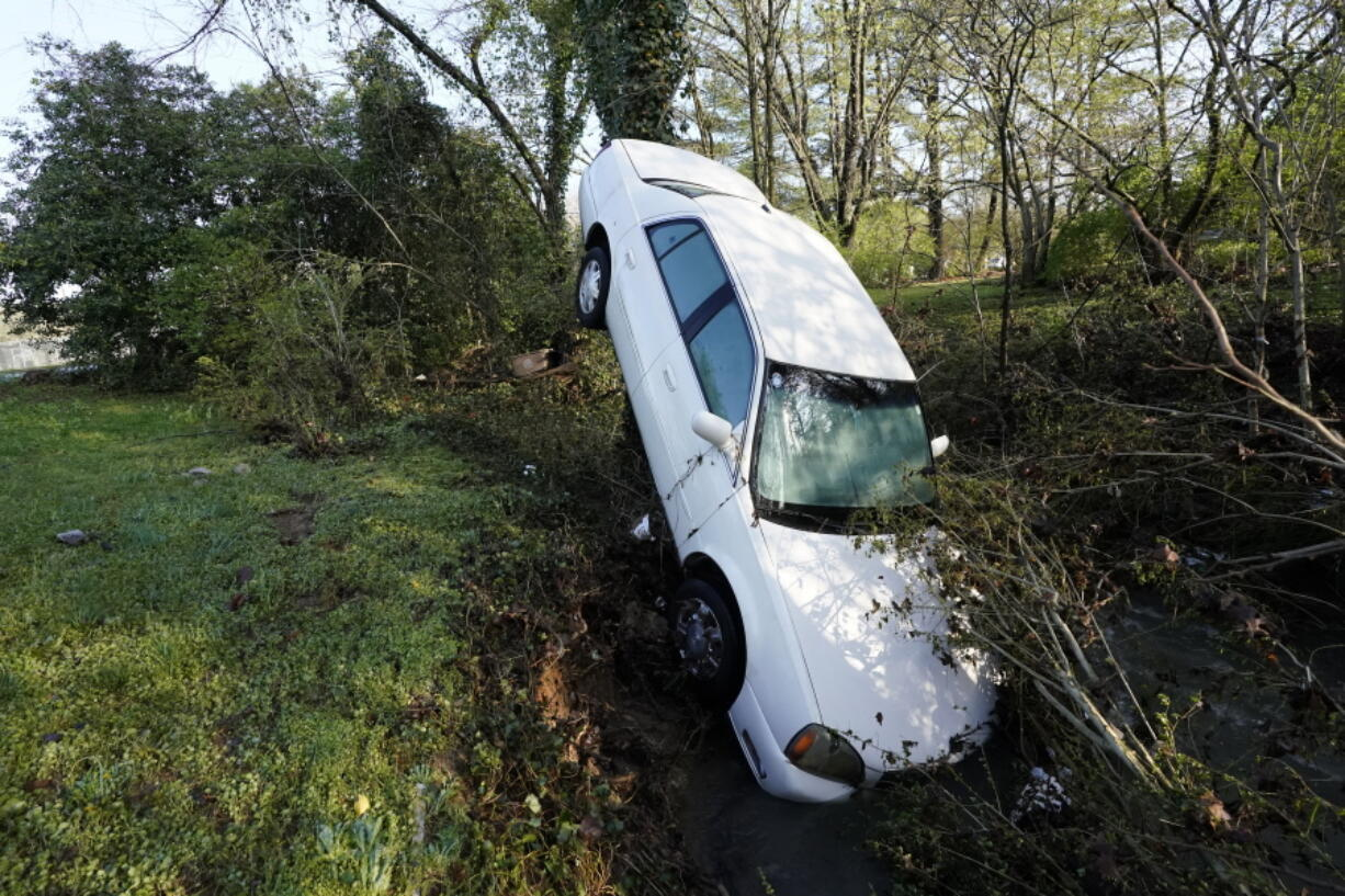 A car that was carried by floodwaters leans against a tree in a creek Sunday, March 28, 2021, in Nashville, Tenn. Heavy rain across Tennessee flooded homes and roads as a line of severe storms crossed the state.