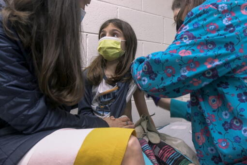 In this Wednesday, March 24, 2021 image from video provided by Duke Health, Alejandra Gerardo, 9, looks up to her mom, Dr. Susanna Naggie, as she gets the first of two Pfizer COVID-19 vaccinations during a clinical trial for children at Duke Health in Durham, N.C. In the U.S. and abroad, researchers are beginning to test younger and younger kids, to make sure the shots are safe and work for each age.