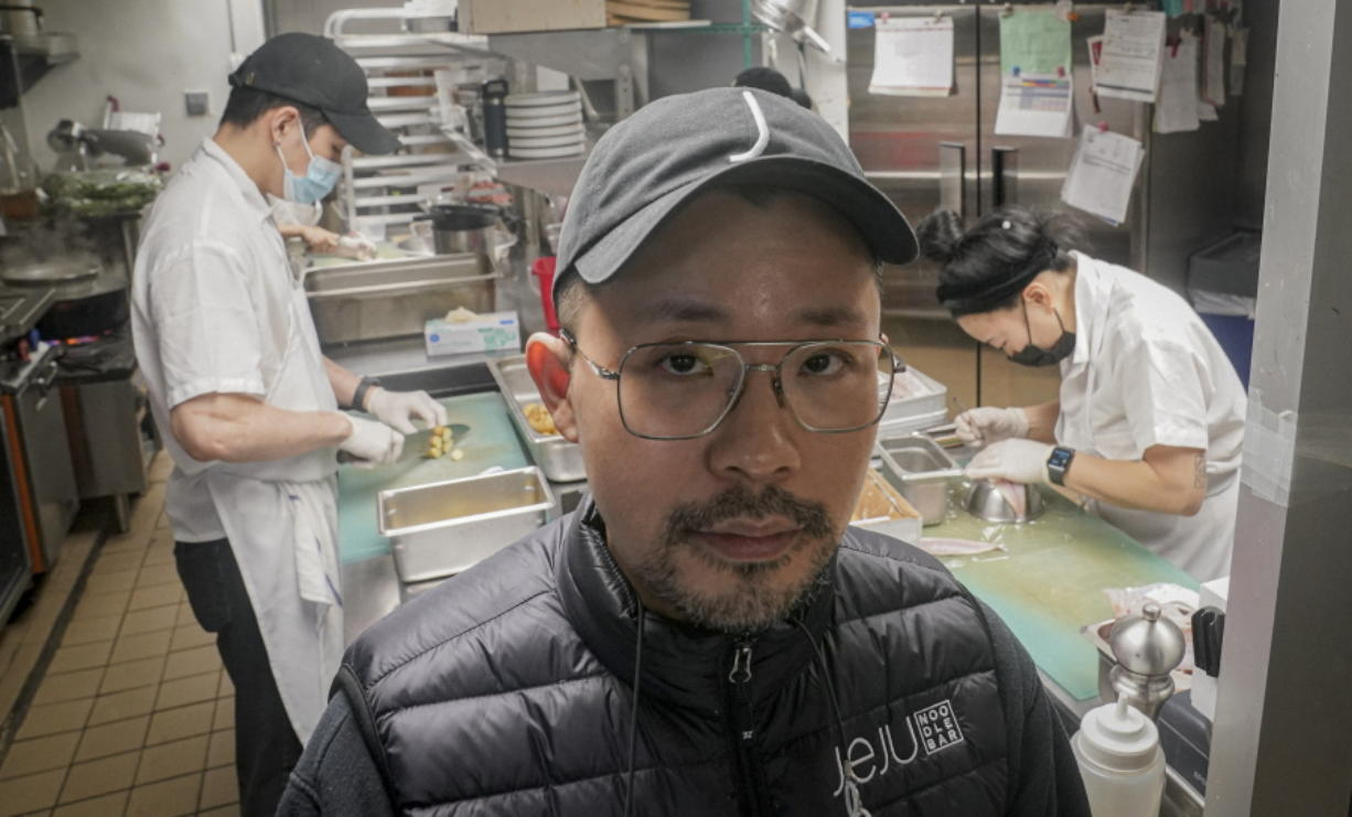 Korean American chef Douglas Kim, center, owner of the restaurant Jeju, which was vandalized during last year's racial injustice protests, is shown in the kitchen as food is being prepped, Saturday Feb. 13, 2021, in New York. Asian Americans have been facing a dangerous climate since the coronavirus entered the U.S. a year ago. A rash of crimes victimizing elderly Asian Americans in the last two months has renewed outcry for more attention from politicians and the media.