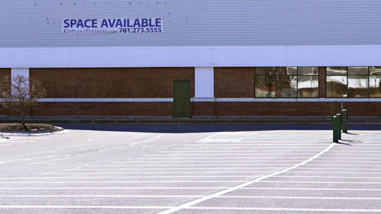 """A """"Space Available"""" real estate sign is posted on the facade of a closed supermarket, Tuesday, March 2, 2021, in Manchester, N.H.  After a year of ghostly airports, empty sports stadiums and constant Zoom meetings, growing evidence suggests that the economy is strengthening. Hiring picked up in February 2021. Business restrictions have eased as the pace of viral infections has ebbed.  Yet the economy remains far from normal."""