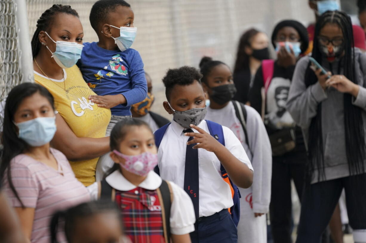 FILE - In this Sept. 9, 2020, file photo, students wear protective masks as they arrive for classes at the Immaculate Conception School while observing COVID-19 prevention protocols in The Bronx borough of New York. Schools and camps across the county are making plans to help kids catch up academically this summer after a year or more of remote learning for many of them.