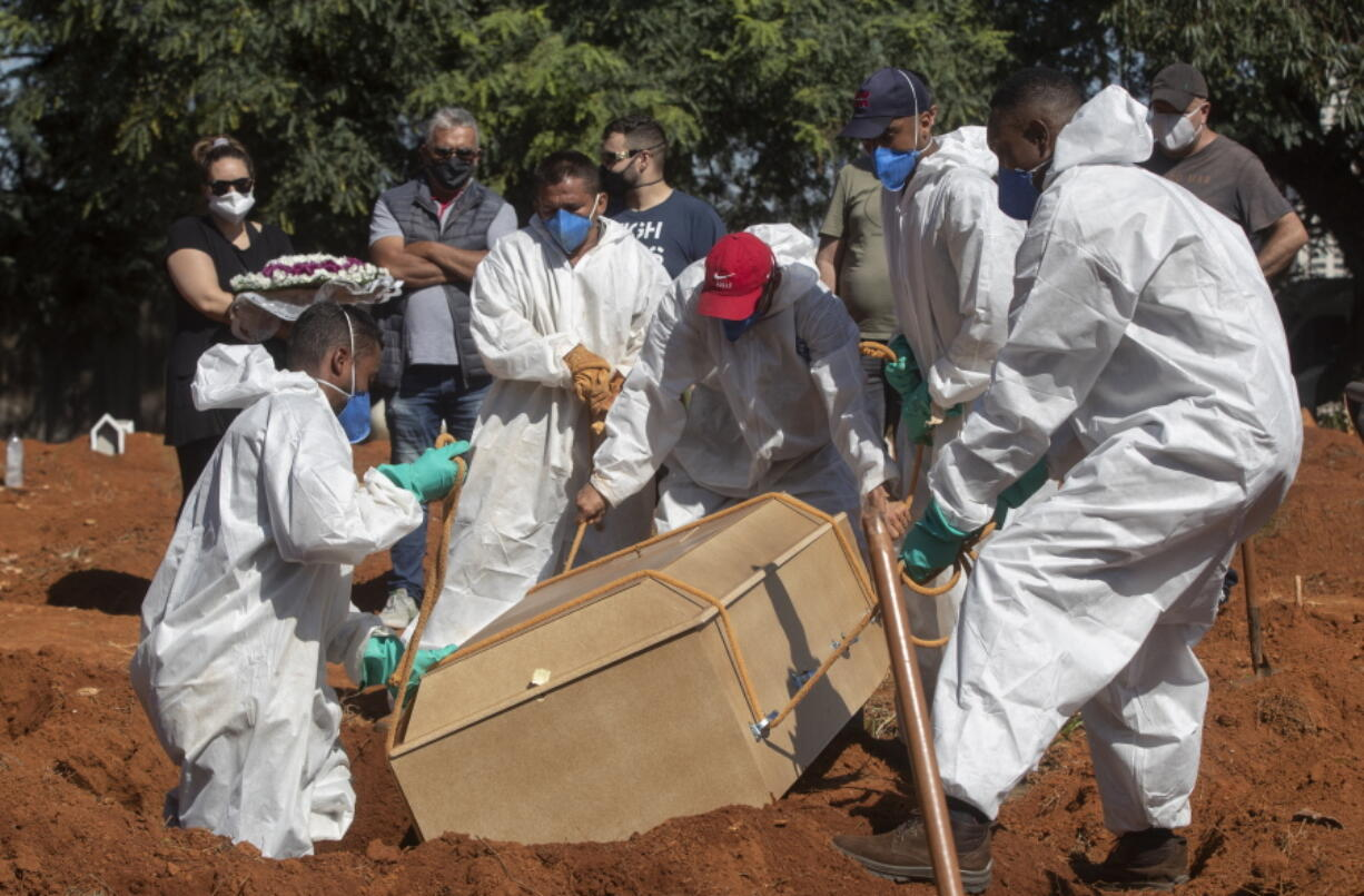 Cemetery workers in full protective gear lower a coffin that contain the remains of a person who died from complications related to COVID-19 at the Vila Formosa cemetery in Sao Paulo, Brazil, Wednesday, March 24, 2021.