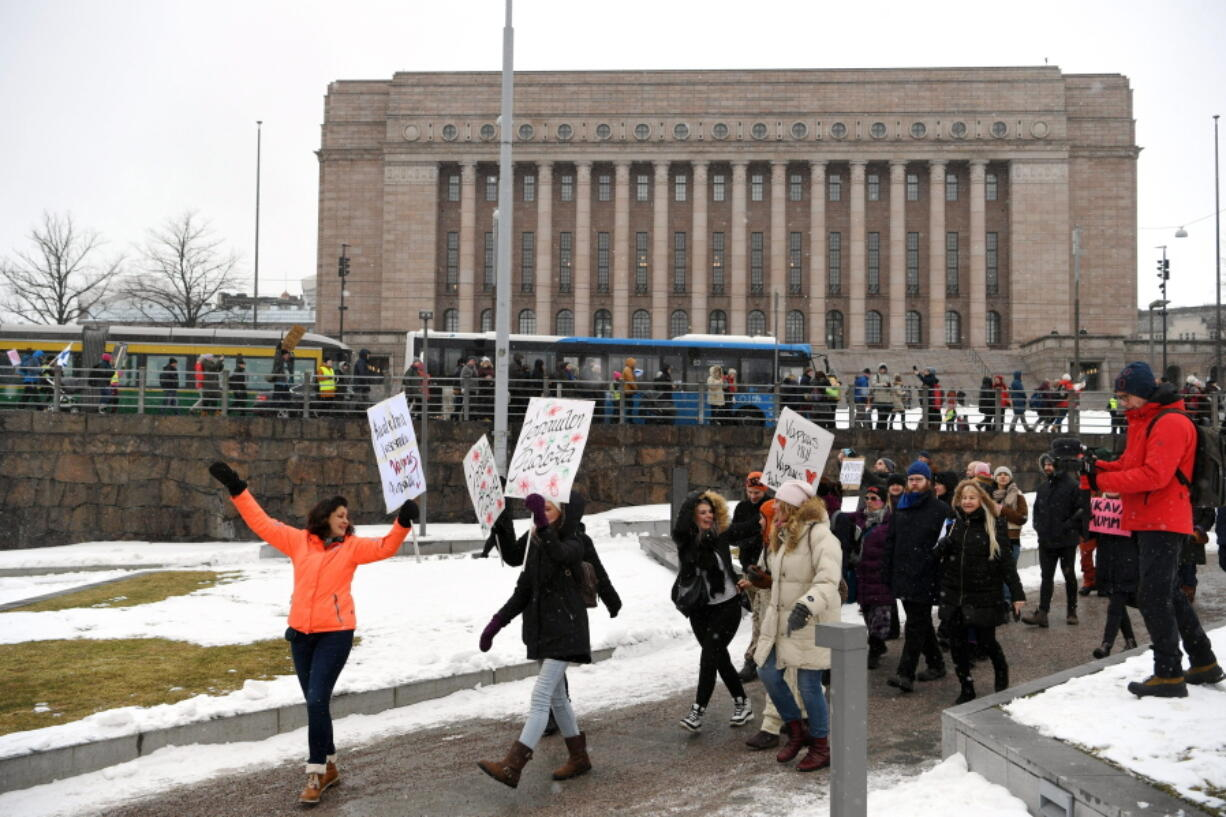 A group of people hold placards during a protest against the Finnish government's regulations to fight the coronavirus pandemic in Helsinki, Saturday, March 20, 2021. Some 400 protesters gathered peacefully in downtown Helsinki.