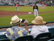 Two older adults, socially distanced, watch a spring training exhibition baseball game between the Pittsburgh Pirates and the Baltimore Orioles on Monday in Bradenton, Fla. (gene j.