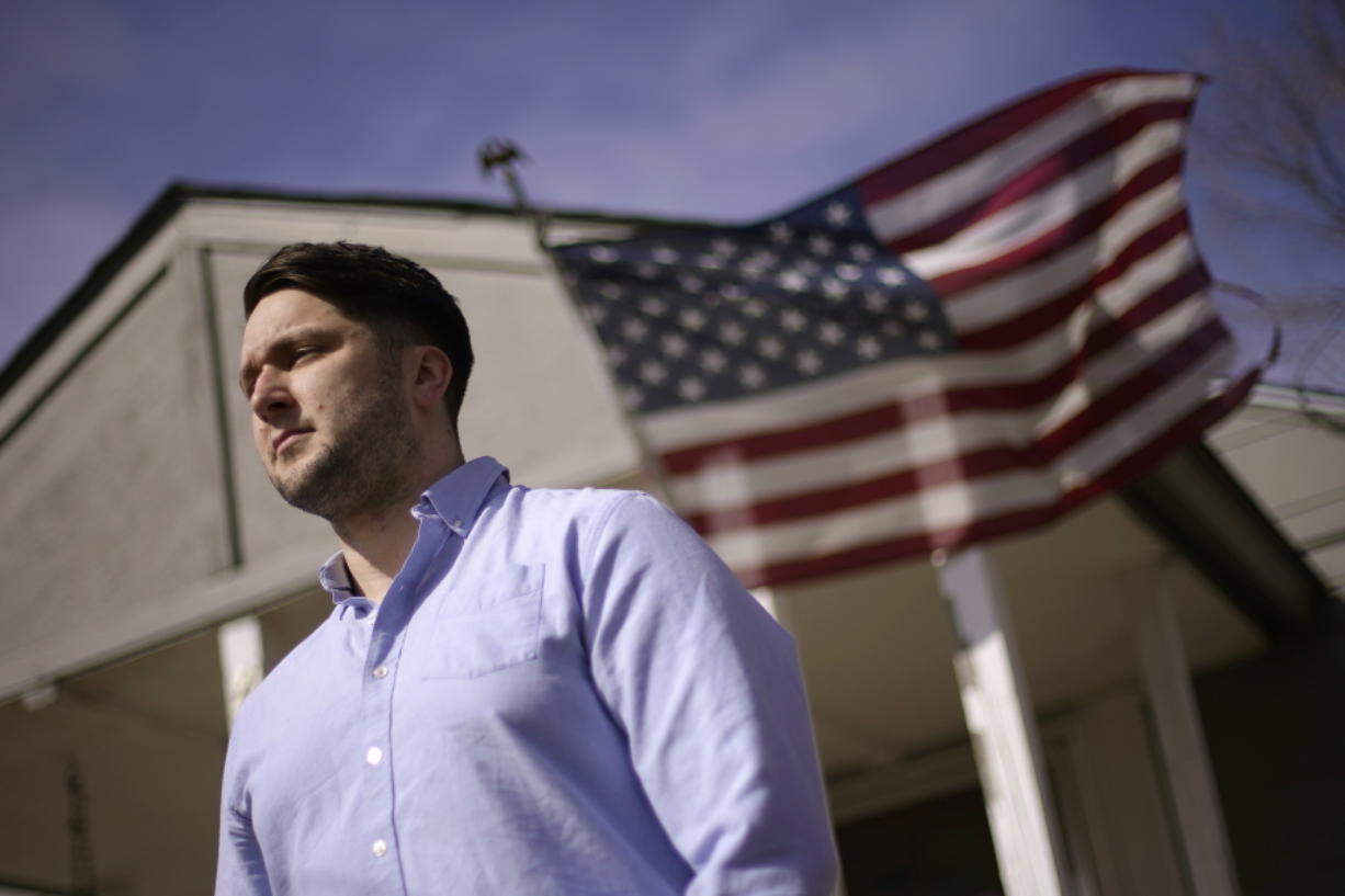 Logan DeWitt stands outside his home Monday, March 8, 2021, in Kansas City, Kan. Because he could work at home, Logan kept his job through the pandemic while his wife lost hers and went back to school. Their financial situation was further complicated with the birth of their daughter nine months ago.