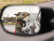 A National Guard soldier directing drivers is reflected in the mirror of a car waiting in a COVID-19 vaccination line Feb. 26, 2021, in Shelbyville, Tenn. Tennessee has continued to divvy up vaccine doses based primarily on how many people live in each county, and not on how many residents belong to eligible groups within those counties.