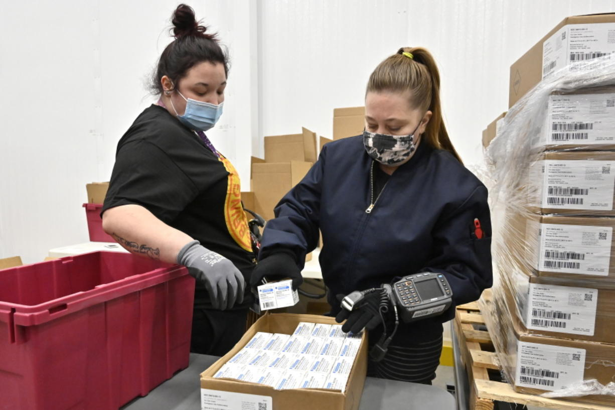 Employees with the McKesson Corporation scan a box of the Johnson &  Johnson COVID-19 vaccine while filling an order at their shipping facility in Shepherdsville, Ky., Monday, March 1, 2021. (AP Photo/Timothy D.