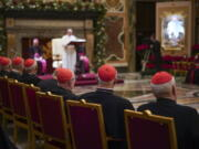 Cardinals listen Dec. 21, 2019, as Pope Francis, background, delivers his Christmas greetings to the Roman Curia, in the Clementine Hall at the Vatican.