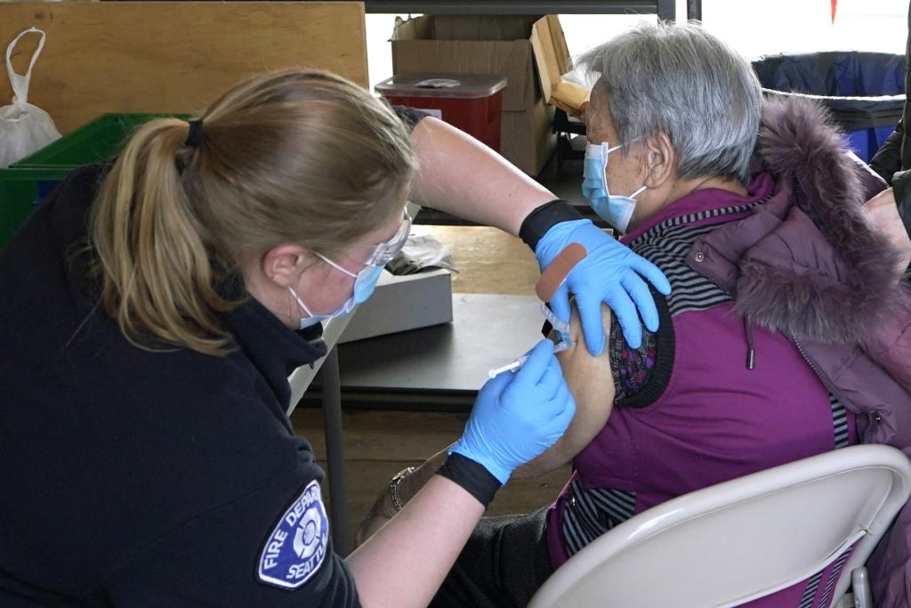 Kristin May, left, an EMT with the Seattle Fire Dept., gives the first dose of the Moderna COVID-19 vaccine to Nu Xiao Jiang, right, Monday, March 1, 2021, at a City of Seattle community COVID-19 testing and vaccination clinic in Seattle's Rainier Beach neighborhood. Seattle Mayor Jenny Durkan announced Monday that the city's COVID-19 vaccination efforts would be expanding in the coming weeks as more doses become available, including the use of the events center at Lumen Field — the home of the NFL football Seattle Seahawks and the MLS soccer Seattle Sounders — as a mass vaccination site with the capacity to deliver thousands of doses every day. (AP Photo/Ted S.