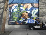 """A cart carries a sign that reads """"Community Vaccination Site,"""" past a photo of a Seattle Seahawks fan, Saturday, March 13, 2021, on the first day of operation of a mass COVID-19 vaccination site at the Lumen Field Events Center in Seattle, which adjoins the field where the NFL football Seahawks and the MLS soccer Seattle Sounders play their games. The site, which is the largest civilian-run vaccination site in the country, will operate only a few days a week until city and county officials can get more doses of the vaccine. (AP Photo/Ted S."""