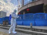 FILE - In this file photo dated Saturday, Feb. 6, 2021, a worker in protectively overalls and carrying disinfecting equipment walks outside the Wuhan Central Hospital where Li Wenliang, the whistleblower doctor who sounded the alarm and was reprimanded by local police for it in the early days of Wuhan's pandemic, worked in Wuhan in central China. A lengthy written report published Thursday March 25, 2021, from a team of international and Chinese scientists on a joint mission to Wuhan aims to help unearth the origins of the coronavirus since it was first detected in China more than a year ago.