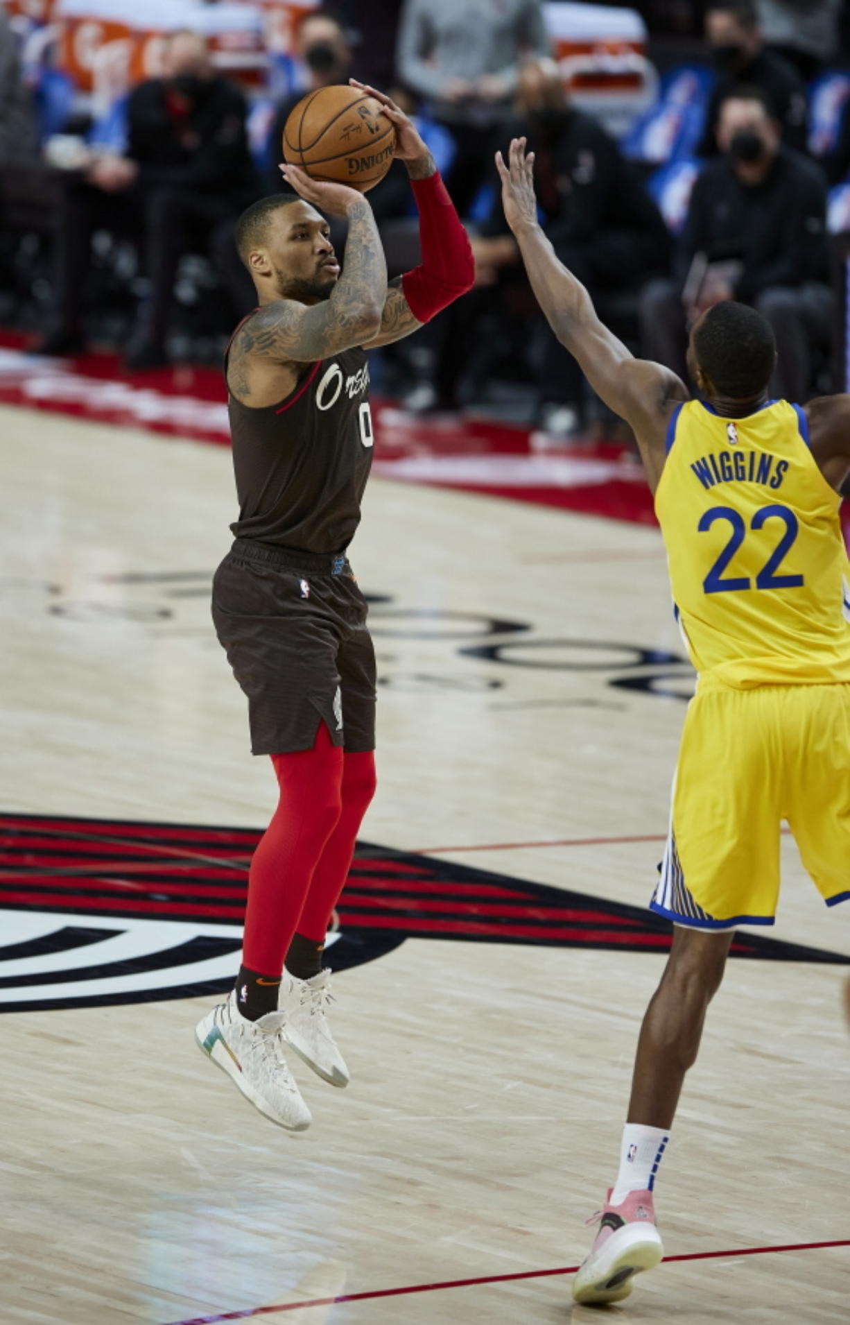 Portland Trail Blazers guard Damian Lillard shoots a 3-point basket over Golden State Warriors forward Andrew Wiggins during the second half of an NBA basketball game in Portland, Ore., Wednesday, March 3, 2021.