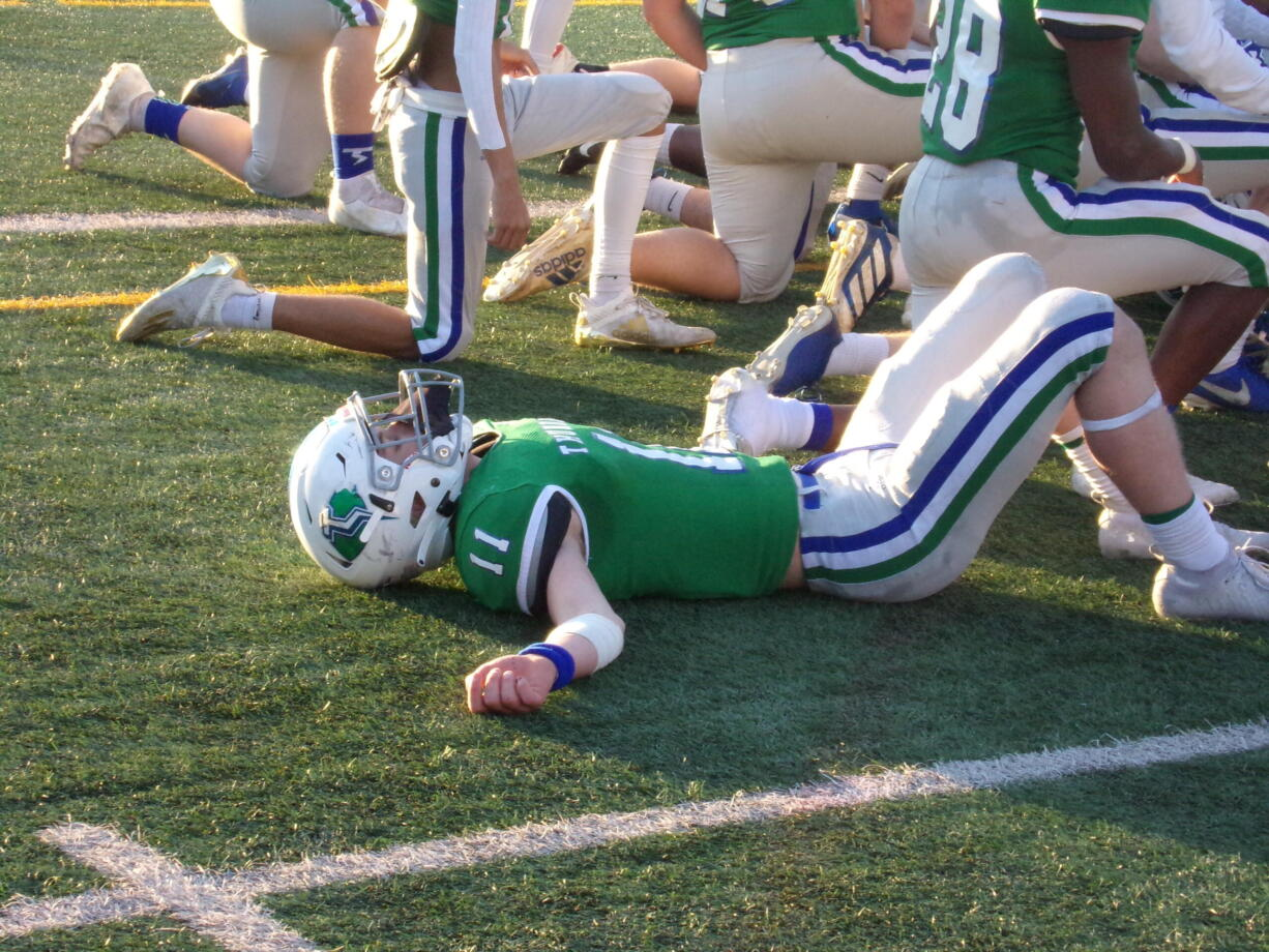 An exhausted Zak Gable lies on the McKenzie Stadium turf after Mountain View's 30-24 win in overtime against Prairie (Tim Martinez / The Columbian)