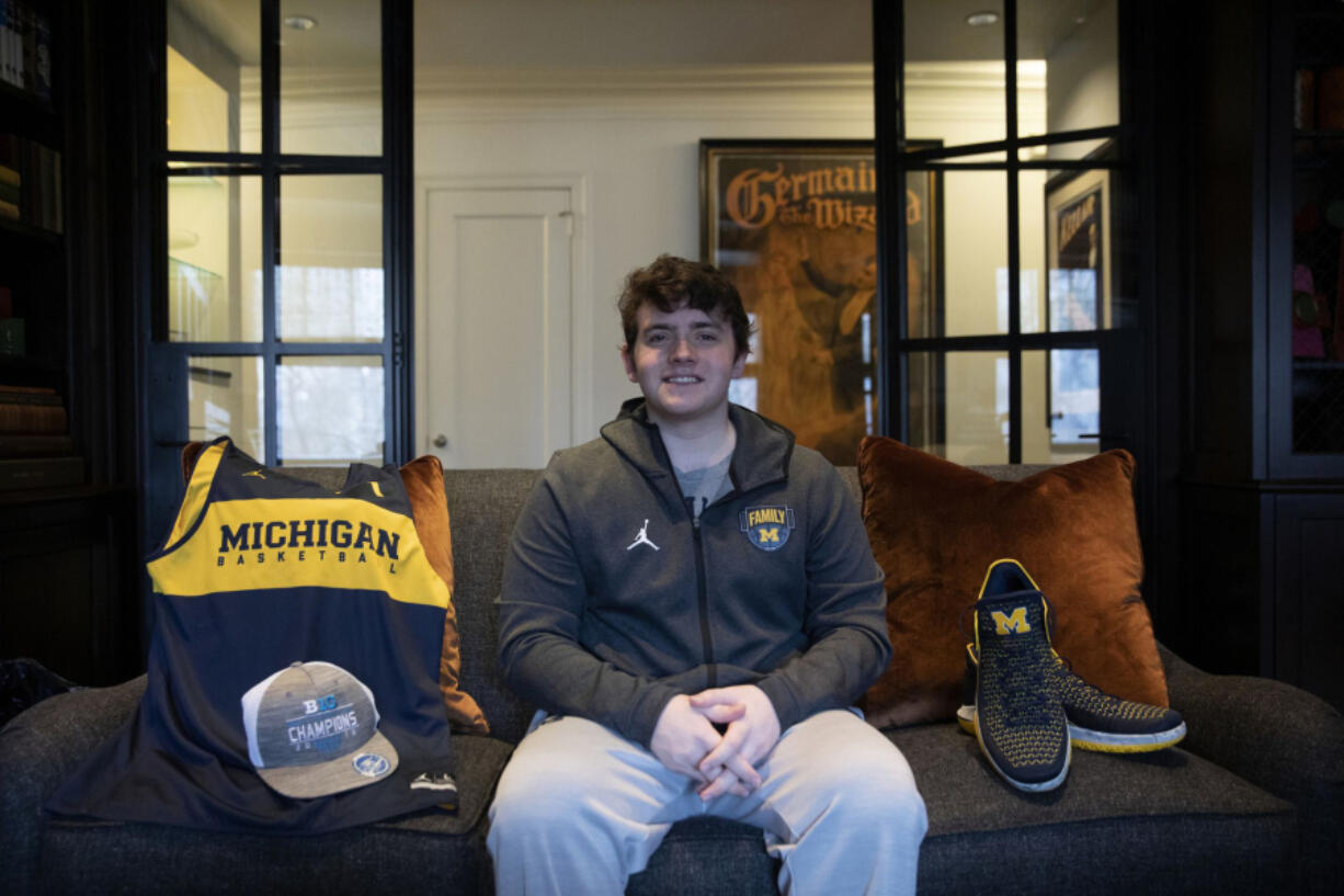 Jason Lansing, 22, a University of Michigan senior from Chicago, sits with some of his Michigan gear for his online business selling game-worn sports gear in partnership with former college athletes on March 25, 2021, in Chicago. The Players Trunk, which stores merchandise in a suburban family garage, is growing so fast it was recently funded by a Chicago venture capital firm.