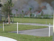 A Rosenwald Elementary School teacher took this undated photo of a sugar cane field burn on a school day just outside the fence surrounding the school grounds in South Bay.