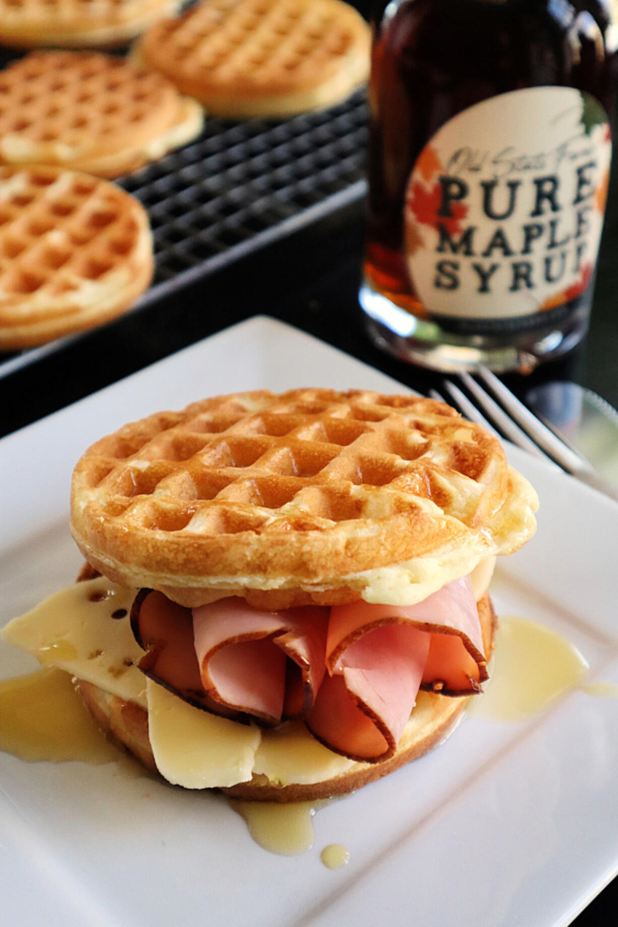 A drizzle of real maple syrup gives a ham and cheese waffle sandwich a sweet finish.