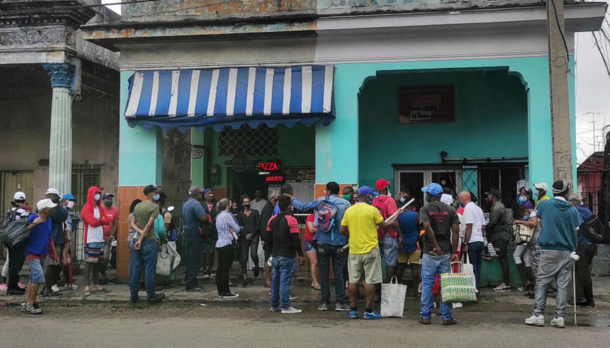 People wearing face masks as a precautionary measure against the spread of the novel coronavirus, COVID-19, queue to buy food in Havana, Cuba on March 22, 2021.