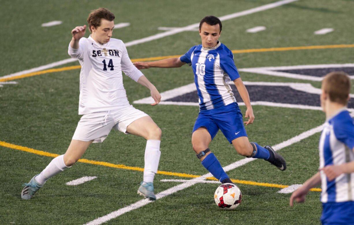 La Center's Angel Merino (10) dribbles past Seton Catholic's Dennis Babiy (14) during a Trico League matchup last week. Merino, an exchange student from Madrid, Spain, is receiving a truly American experience through high school sports.