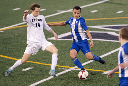 La Center's Angel Merino (10) dribbles past Seton Catholic's Dennis Babiy (14) during a Trico League matchup last week. Merino, an exchange student from Madrid, Spain, is receiving a truly American experience through high school sports. (Joshua Hart/The Columbian)