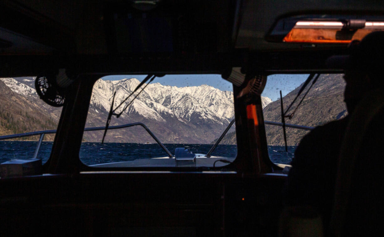 Mountains of the North Cascades in the distance as Ray Eickmeyer and Mistaya Johnston travel by boat to vaccinate those at Holden Village, Stehekin and workers at a mine remediation water treatment plant operated by Rio Tinto, on Tuesday, March 30, 2021.