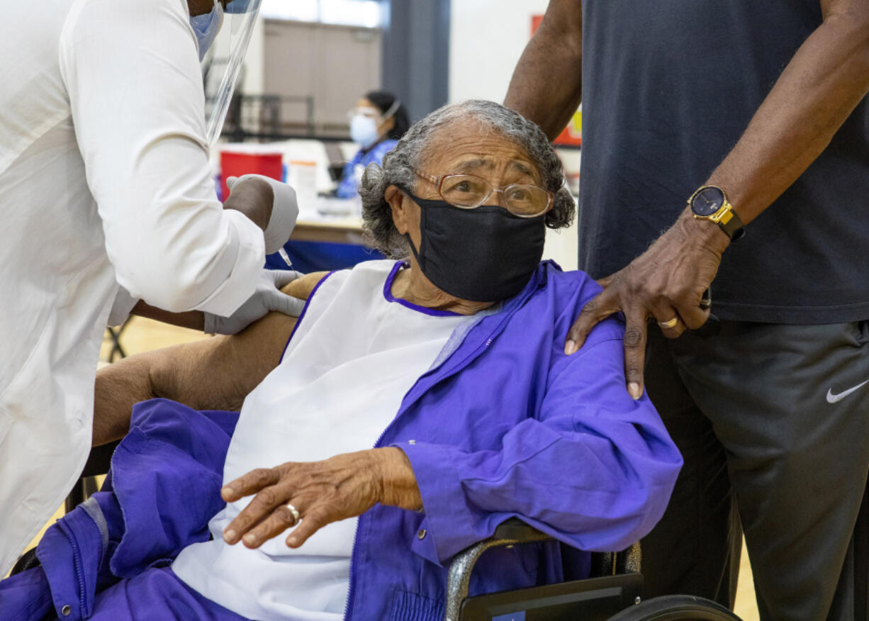 Former educator Nancy Dawkins, 97, who worked for Miami-Dade County Public Schools for more than 30 years, reacts to receiving a vaccine at the new FEMA-supported, state-run COVID-19 vaccine satellite site inside the Samuel K. Johnson Youth Center at Charles Hadley Park in Liberty City, Florida, on Friday, March, 19, 2021. (Daniel A.