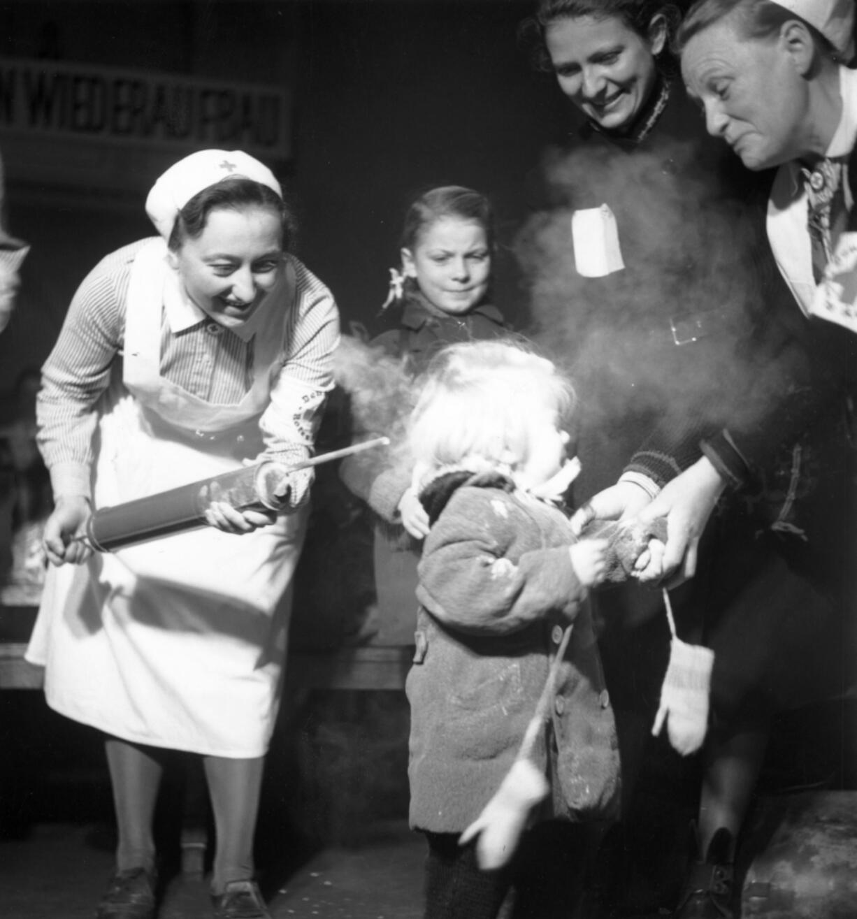 October 1945:  A child crying as she is sprayed with DDT delousing powder at Nikolsburger Platz School, Wilmsdorf, Germany.