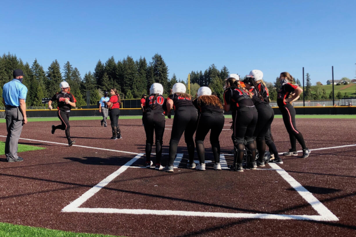 Battle Ground softball players greet Candice Adams at home plate after she hit a grand slam in the Tigers' 17-4 win over Camas on Wednesday at Camas High School (Micah Rice/The Columbian).