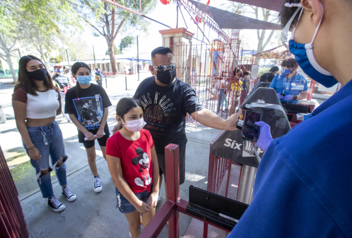 Customer Cesar Romero, with niece Valeria Ocampo, holds his phone showing a bar code so that it can be scanned by employee Daniel Abidin, right, at the entrance to Six Flags Magic Mountain in Valencia, California, which re-opened on April 2, 2021, after more than a year of being closed due to the coronavirus outbreak.