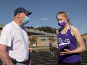 Columbia River volunteer coach Rick Sloan instructs freshman Logan DeJong, his eldest granddaughter, during a 2A Greater St. Helens League meet at Woodland High School. Sloan, 74, was a participant at the 1968 Summer Olympics in Mexico City, placing seventh in the decathlon. He went on to have a 41-year coaching career at Washington State.