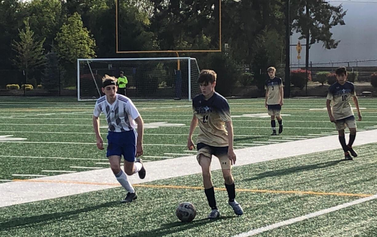 Seton Catholic's Gavin Erickson dribbles past an Elma defender during Thursday's 1A boys soccer district semifinal at Seton Catholic. The Cougars won 6-0.
