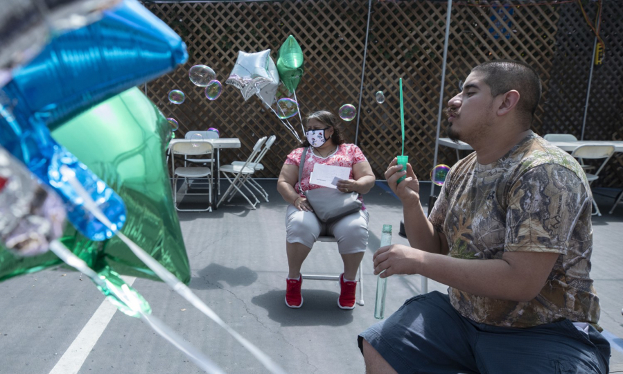 Daniel Arana, 20, blows soap bubbles in the post-shot waiting area with his mother Yolanda following his mock vaccination April 11 at Friendship Foundation in Redondo Beach, Calif. (Myung J.