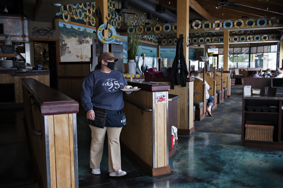 Beaches server April Martinell brings a plate of bread to customers. Restaurants returned to limited indoor dining in February.
