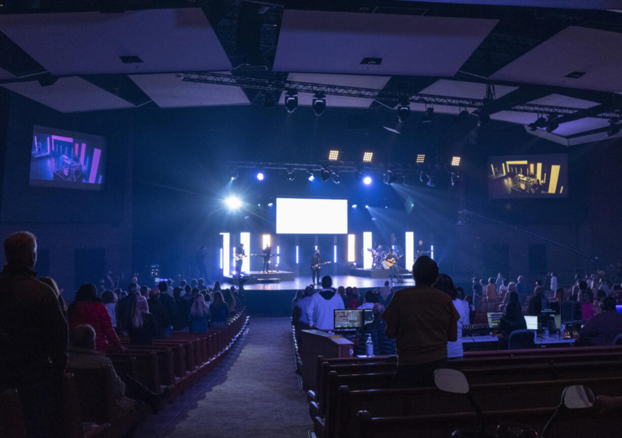 Blue lights illuminate a rocking Palm Sunday service and reduced-capacity congregation at Crossroads Community Church.