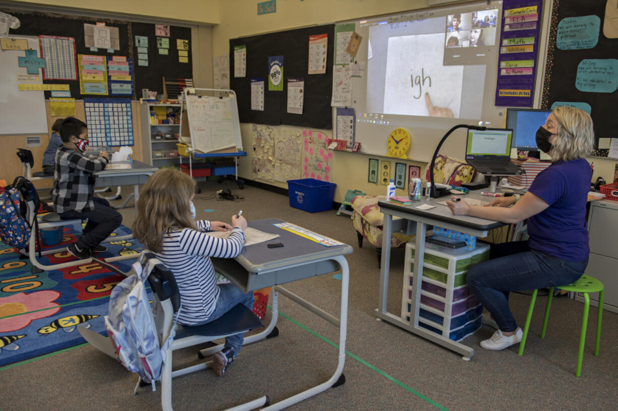 First-graders Jared Perez Bello, 7, from left, and Amelia Perkins, 6, take part in a lesson as classmates at home join remotely with teacher Tiffany Martinson at Washington Elementary School in Vancouver. When Clark County school districts transitioned to hybrid instruction in January, for many teachers, it included teaching simultaneously to two sets of students: in-person and virtually through Zoom. Now, Clark County districts are making another change after new state guidance allows for more spacing in classrooms between students.