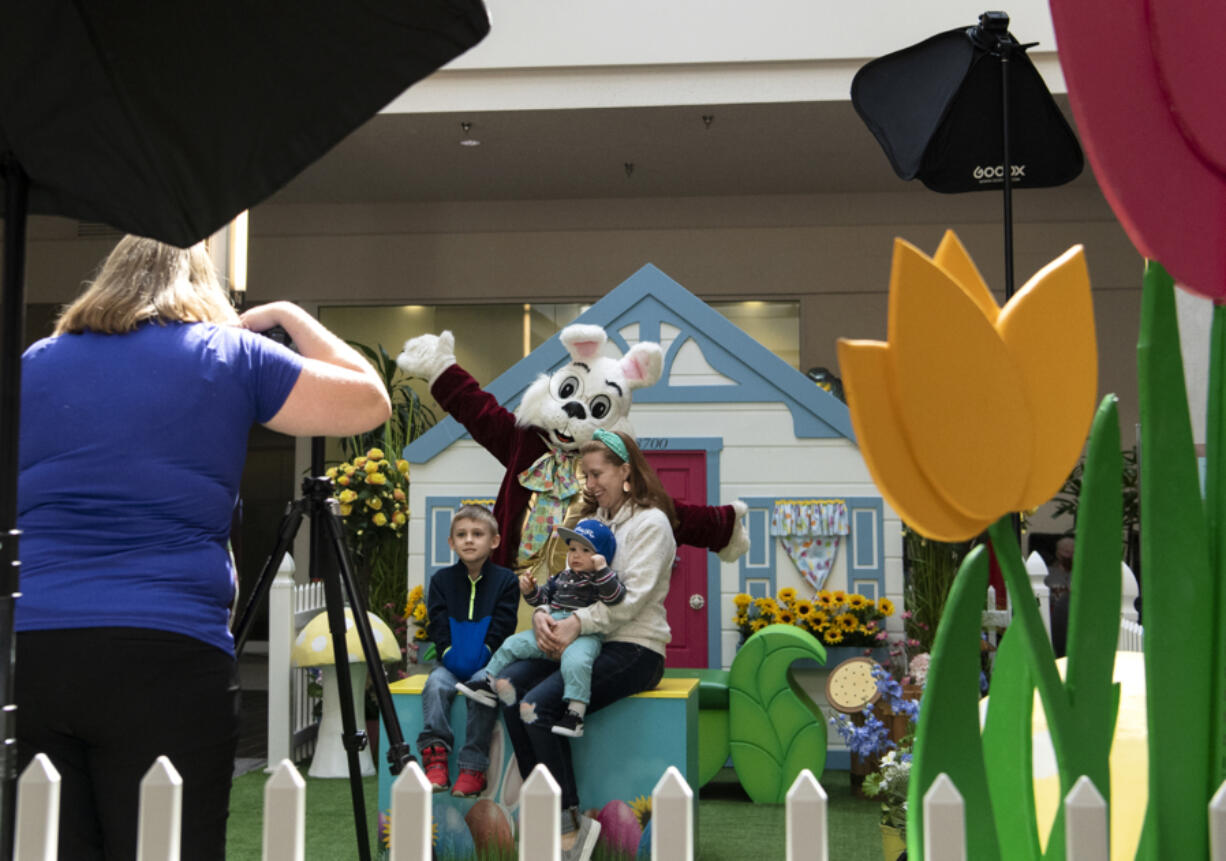 Melissa Brewer of 4Ever Photography snaps a shot of the Dees family - which includes 5-year-old Miles, 11-month-old Zane and mom Renee - with the Easter Bunny on Saturday at the Vancouver Mall.