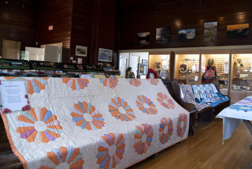 Quilts line the pews on Saturday at the North Clark Historical Museum in Amboy. This quilt pictured was recently donated by 101-year-old Elaine Fletcher. Her mother crafted the mostly finished quilt; a needle was found in the unfinished binding.