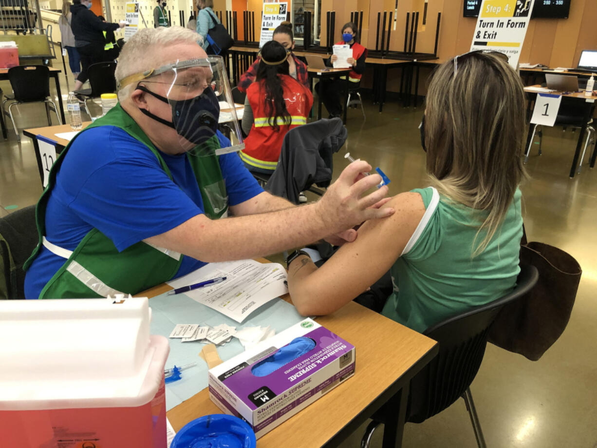 Jack Stump injects COVID-19 vaccine at a vaccination clinic at Woodland High School.