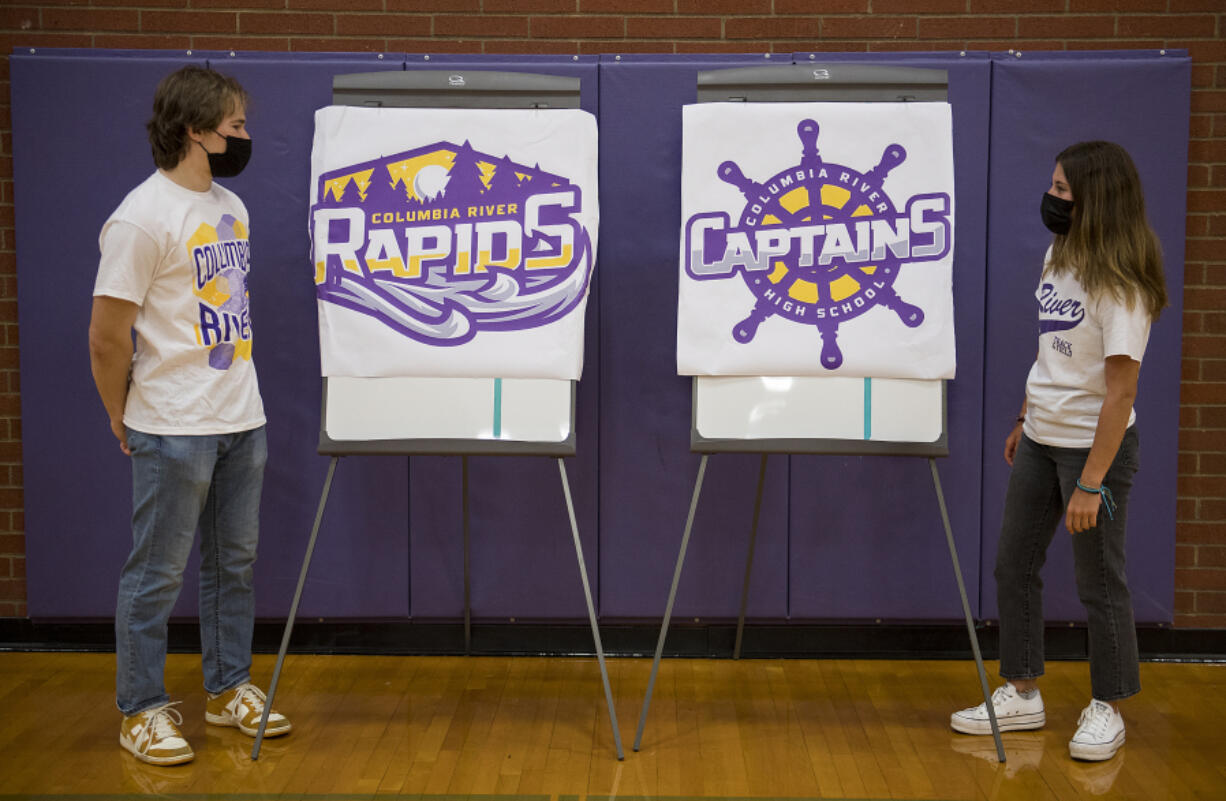 Columbia River High School seniors Keith Blau, 18, and Luci Ianello, 17, look over choices for the school's new mascot, the Rapids or the Captains, while pausing for a photo in the school's gym.
