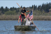 Conan Reutov, left, hauls a carp out of Vancouver Lake on Wednesday with the help of Arty Kuzmin.