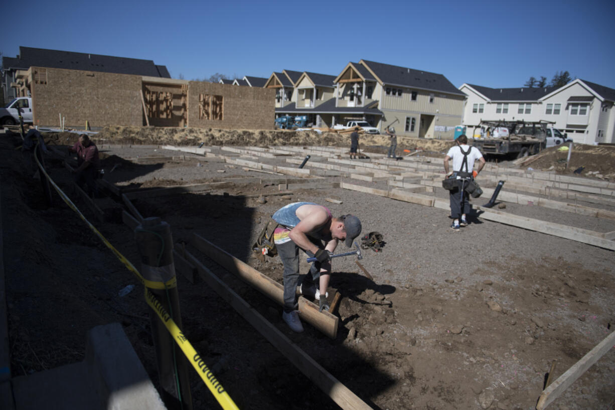 Russell Hines of Brothers Concrete Inc., foreground, helps to build a triplex at the 2 Creeks development in Camas on Wednesday. Clark County's housing market is facing a record low supply, and industry professionals say it's not that new listings have dried up or the pace of building has slowed down - it's just that there's no way to keep up with the current level of demand.