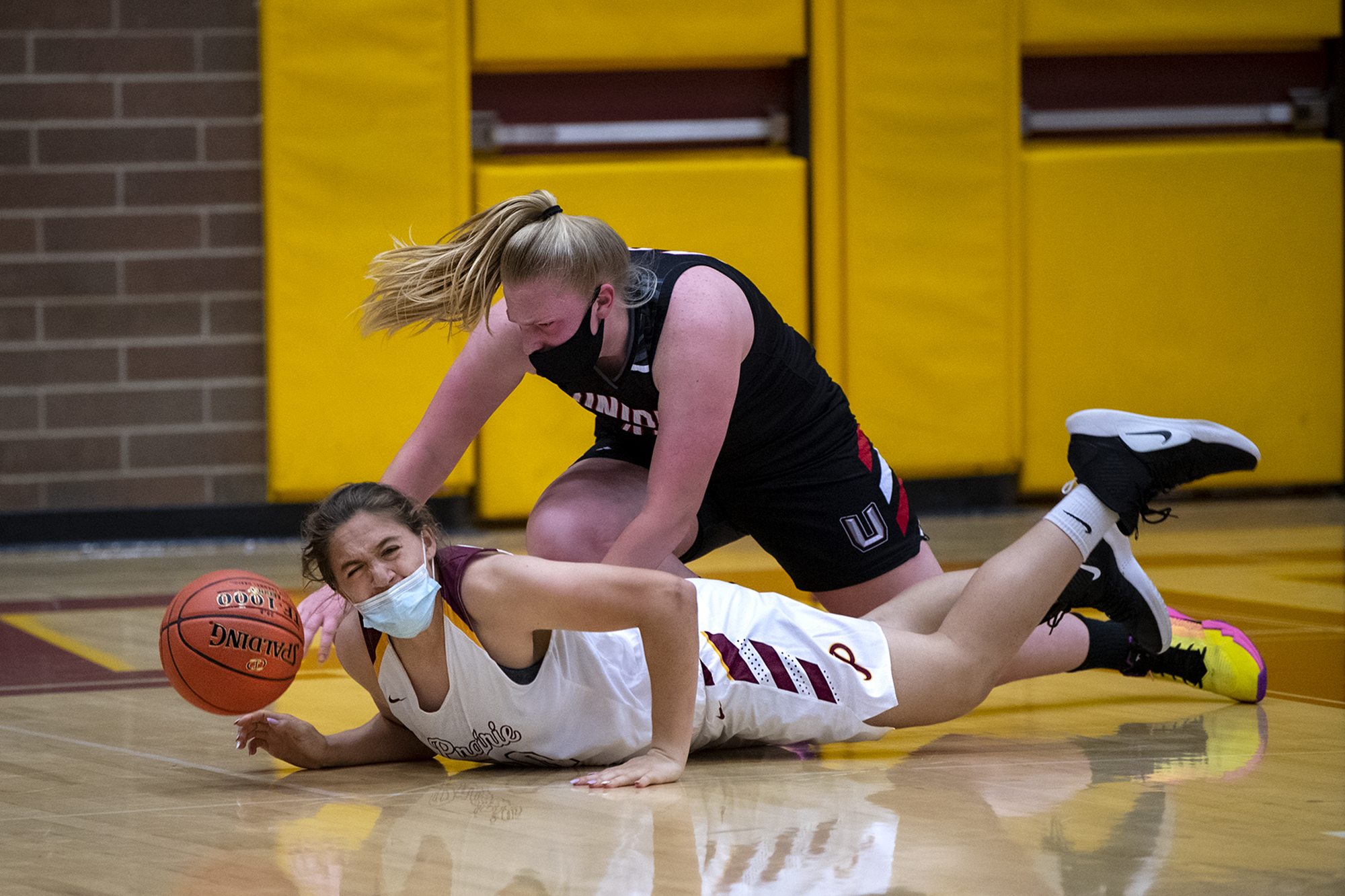 Prairie's Alysia Fraly, bottom, falls to the ground after colliding with Union's Ariel Ammentorp while they battled for a rebound in a 4A/3A Greater St. Helens League girls basketball game on Thursday, April 22, 2021, at Prairie High School. Union won 50-46.
