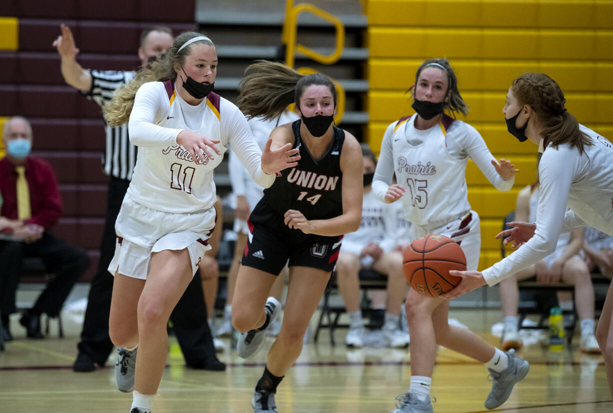Prairie's Claire Heitschmidt fights off the defense of Union's Kaneyl Carpenter to get a handoff from Kaitlyn Caughey in a 4A/3A Greater St. Helens League girls basketball game on Thursday, April 22, 2021, at Prairie High School. Union won 50-46.