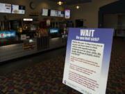 A sign in the entryway alerts customers to COVID-19 restrictions at Battle Ground Cinema. Clark County movie theaters are reopening, but owners are still waiting on a federal grant program intended to help them stay afloat.