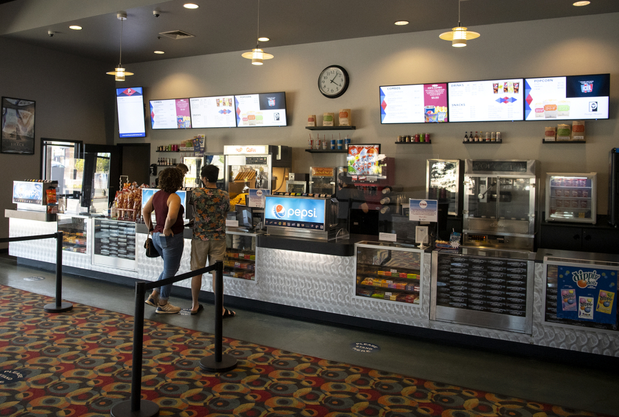 A pair of moviegoers wait for their concessions on Wednesday at Battle Ground Cinema. The multiplex was one of a handful of local theaters that reopened earlier this month.