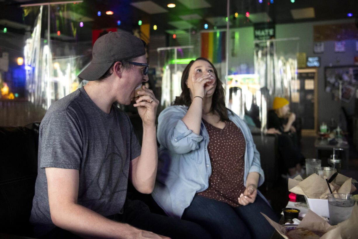 Vancouver residents Josh Golliday, left, and his sister Katherine Golliday take jello shots at Vault 31 Bar in Vancouver. Vault 31 is giving away free jello shots to guests who can prove they have received a COVID-19 vaccination. A vaccination card or a selfie of getting vaccinated both serve as proof.