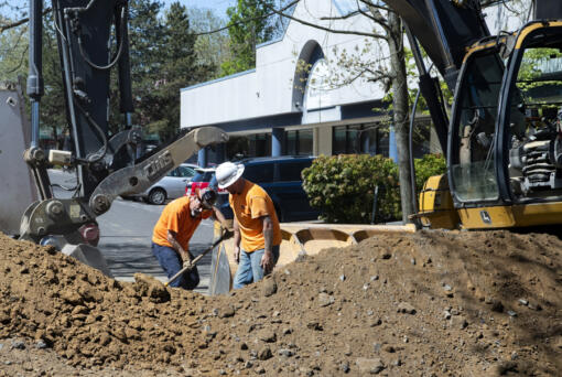 A pair of construction workers shovel large chunks of pavement into the excavator on Tuesday at the corner of Broadway and East Mill Plain Boulevard. The work marks the start of a project to replace the sewer and water main lines beneath Broadway, which will continue through the summer.