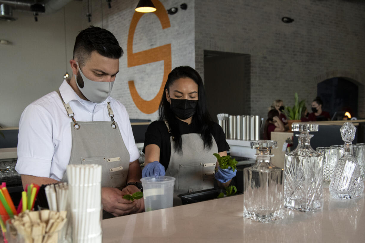Bartender Kegan Duz-Aguilar and bar manager Oula Thepsouvanh prepare mint leaves for the afternoon rush at Saap Fusion Kitchen at Grand Central Retail Center in Vancouver. The restaurant recently opened in the space formerly occupied by Lapellah and has been transformed thanks to $500,000 in renovations.