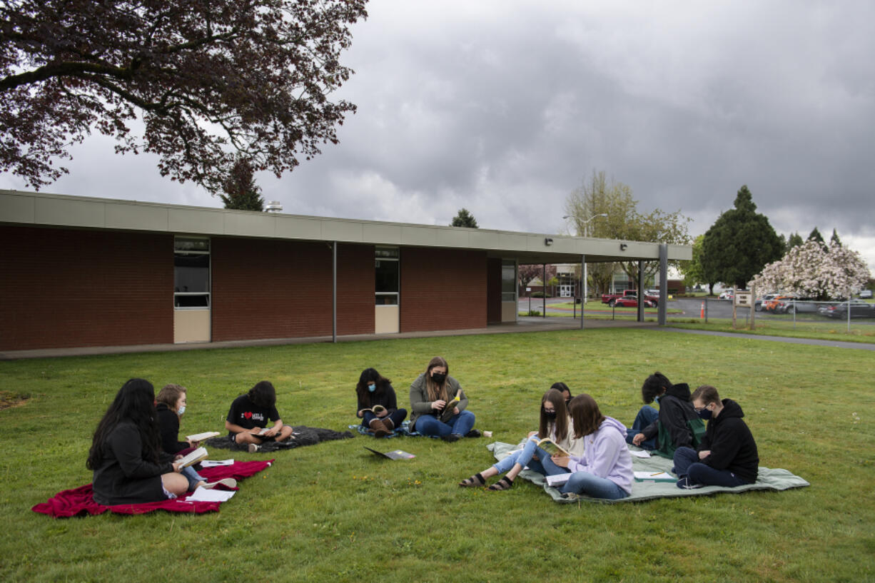 Eighth-graders gather outside on blankets while taking part in an English class with student teacher Megan Collins at Laurin Middle School on Monday morning, April 26, 2021.(Amanda Cowan/The Columbian)