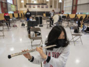 Seventh grader Valyssa Nguyen wears a specialized band mask and a cover on the end of her flute for COVID-19 protections during band class Monday morning at Laurin Middle School.
